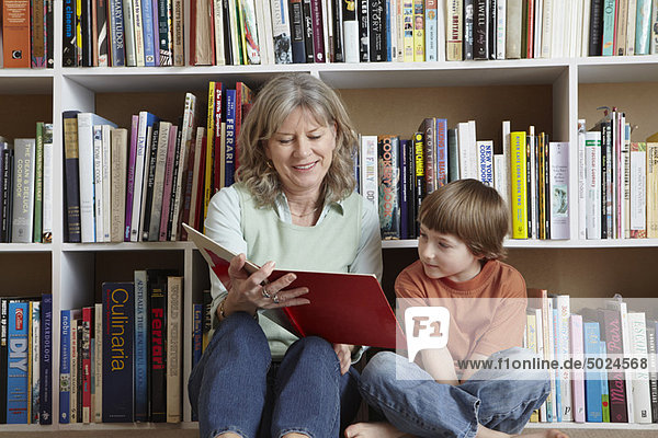 Woman reading with grandson by bookshelf