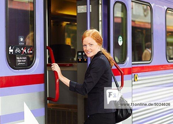 junge Frau junge Frauen einsteigen lächeln Zug