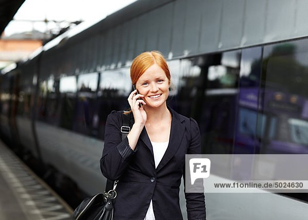 Portrait of young smiling Woman sprechen über Mobile am Bahnhof