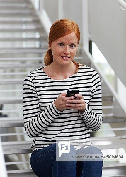 Portrait junge rothaarige Frau Senden von Textnachrichten