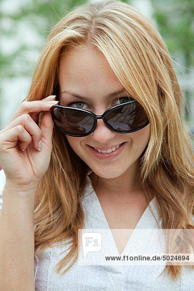 Portrait einer lächelnden Frau mit Sonnenbrille