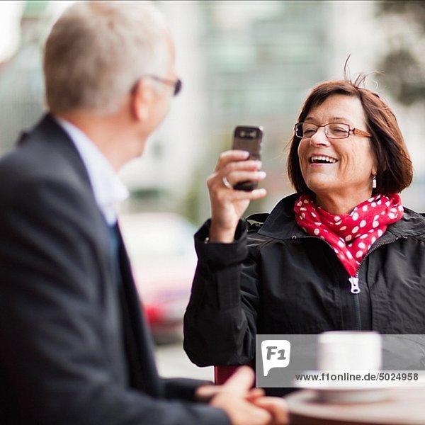 Frauen fotografieren Mann mit Handy  lächelnd