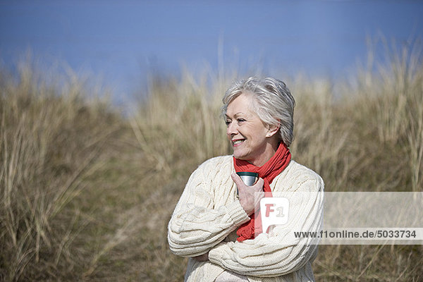 A senior woman sitting amongst the sand dunes, holding a hot drink LV14850057