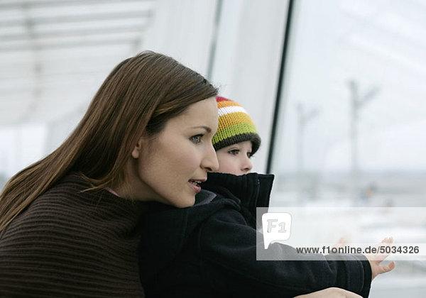 Mutter und Sohn sehen nach draußen  Flughafen München  Bayern  Deutschland