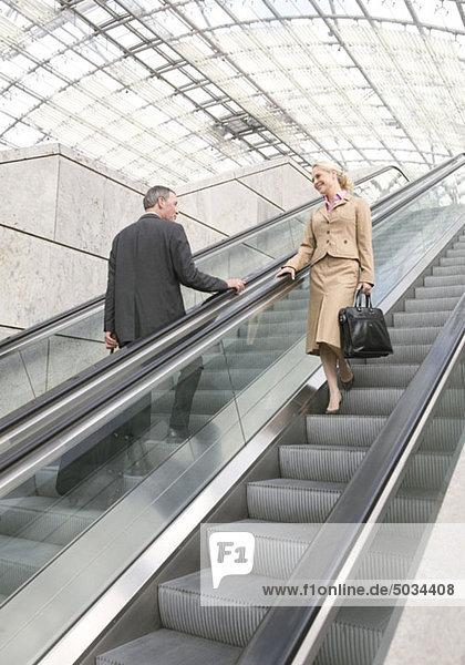Geschäftsmann und Geschäftsfrau flirten auf Rolltreppe