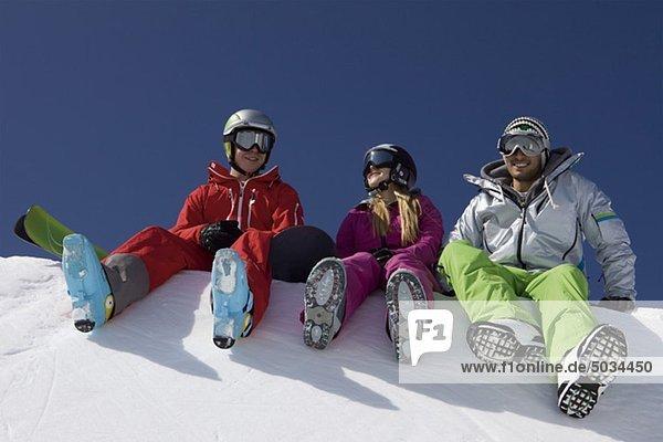 Snowboarder und Skifahrer sitzen an Halfpipe