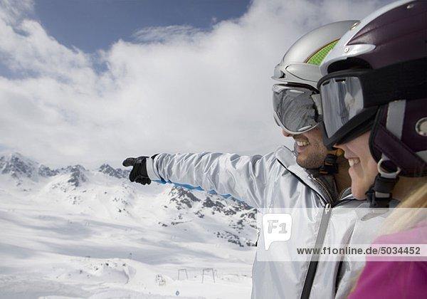 Paar in Skianzügen betrachtet die Aussicht