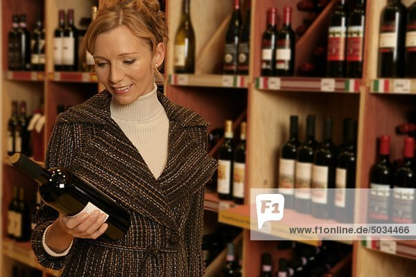 Frau steht vor einem Weinregal und hält eine Weinflasche in der Hand
