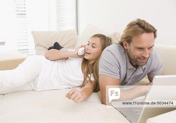 Tochter und Vater mit Laptop und Telefon auf der Couch