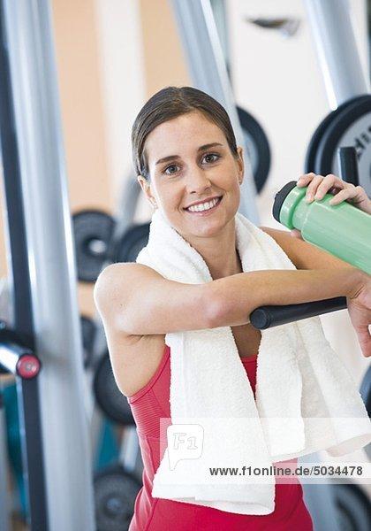 Frau in Fitnessstudio trinkt aus Flasche