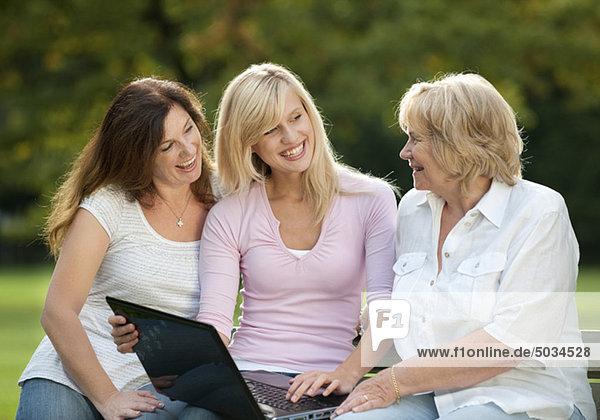 Großmutter  Mutter und Tochter mit Laptop im Park