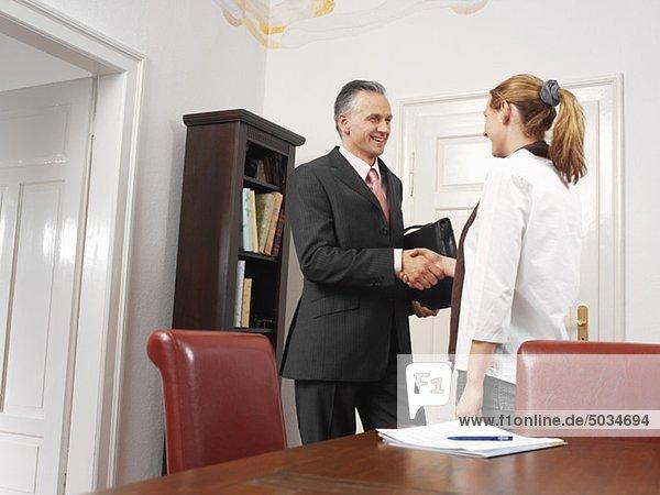 Berater und Frau schütteln Hände im Wohnzimmer