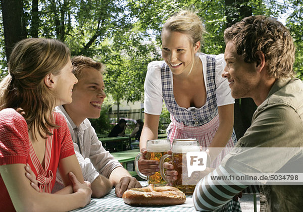 Blonde Bedienung bringt drei jungen Leuten Bier - Biergarten - Sommer