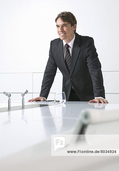 Lächelnder Geschäftsmann an Konferenztisch