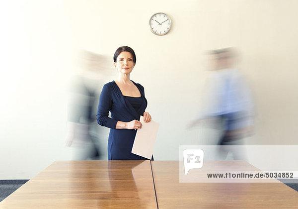 Geschäftsfrau im Konferenzraum mit vorbeigehenden Personen im Hintergrund