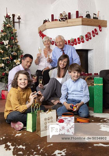 Großeltern  Eltern und Kinder sitzen am Weihnachtsbaum