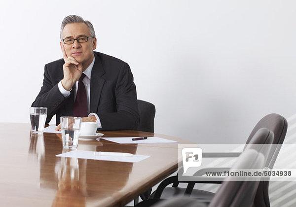Geschäftsmann sitzt in Konferenzraum