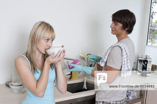 Mann wäscht ab während Frau Kaffee trinkt  München  Bayern  Deutschland