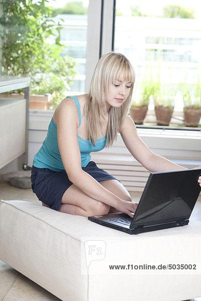 Woman using laptop at home  Munich  Bavaria  Germany