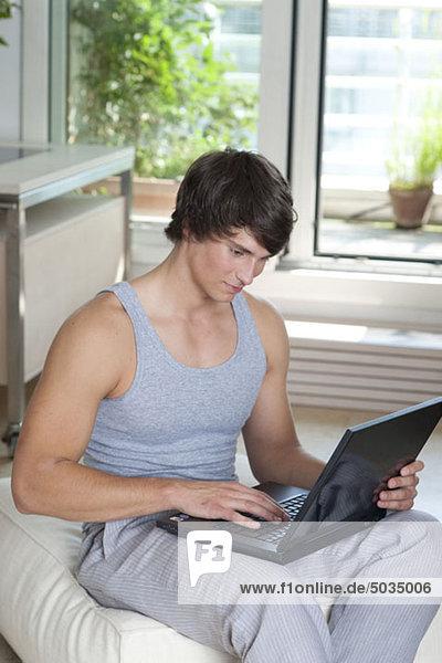 Mann mit Laptop Zuhause  München  Bayern  Deutschland
