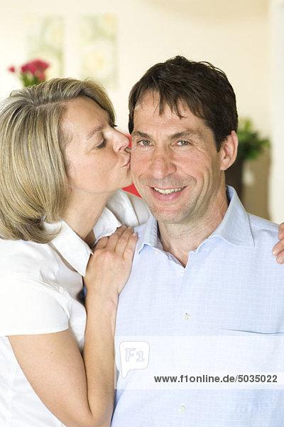 Woman kissing man at home  Munich  Bavaria  Germany