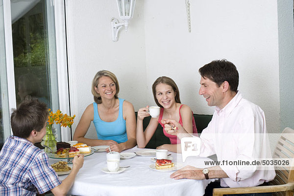 Familie trinkt Kaffee und isst Kuchen auf der Terrasse,  München,  Bayern,  Deutschland