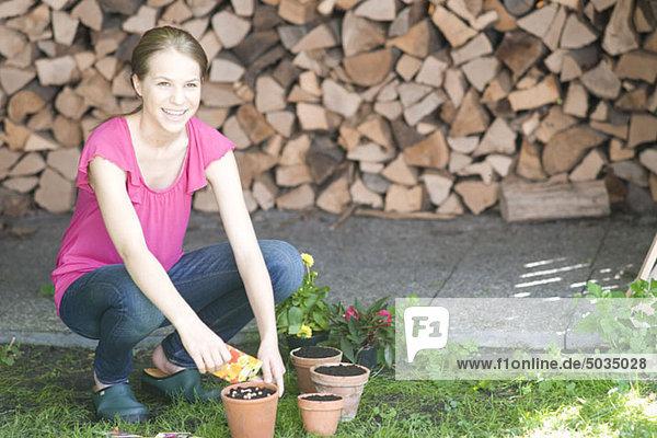 Teenage girl planting potted plant  Munich  Bavaria  Germany