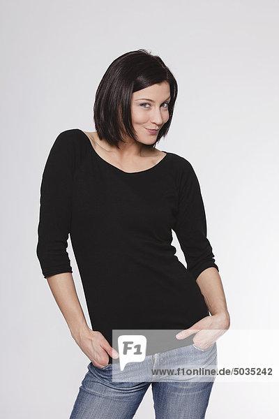 Mittlere erwachsene Frau mit Händen in den Taschen vor weißem Hintergrund  lächelnd  Portrait