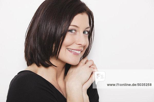 Nahaufnahme einer erwachsenen Frau mit Finger auf der Lippe vor weißem Hintergrund  lächelnd  Porträt