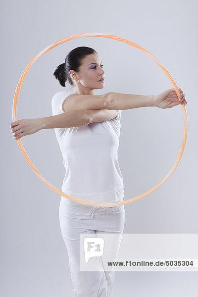 Mittlere erwachsene Frau mit Reifenreifen auf weißem Hintergrund  Portrait