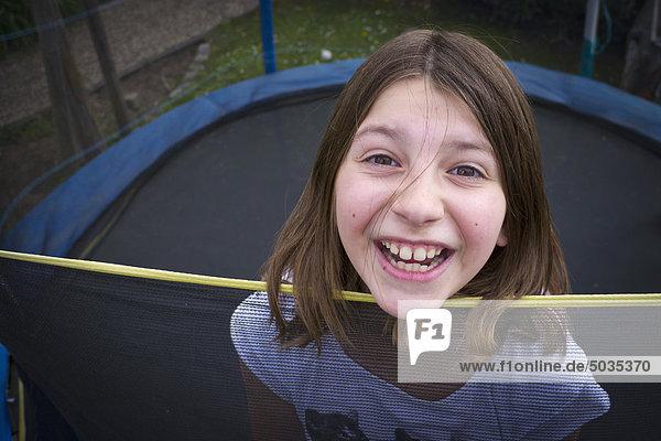 Mädchen springt auf Trampolin  lächelnd  Portrait
