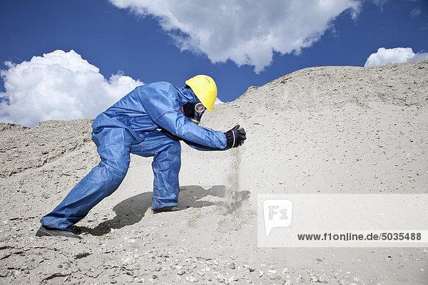 Mann in Schutzkleidung verschüttet Sand auf Sanddüne