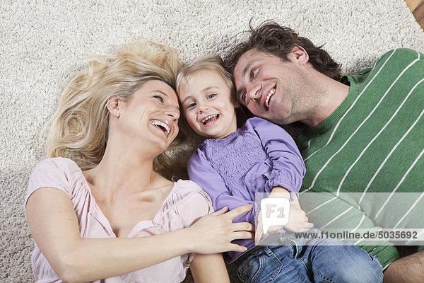Deutschland  Bayern  München  Mutter kitzelt Tochter mit Vater daneben  lachend