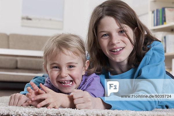 Junge und Mädchen auf Teppich liegend  lächelnd  Portrait