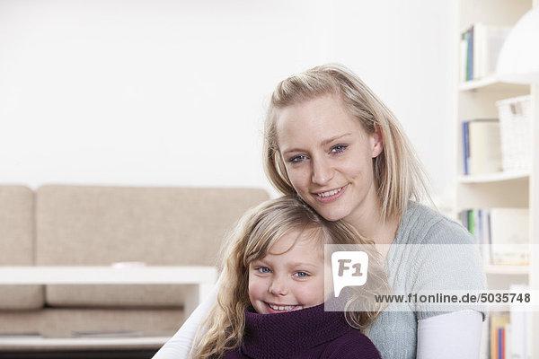 Deutschland  Bayern  München  Mutter und Tochter zu Hause sitzend