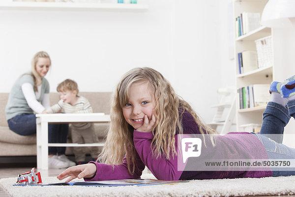 Mädchen mit Buch auf dem Boden  Mutter und Sohn im Hintergrund