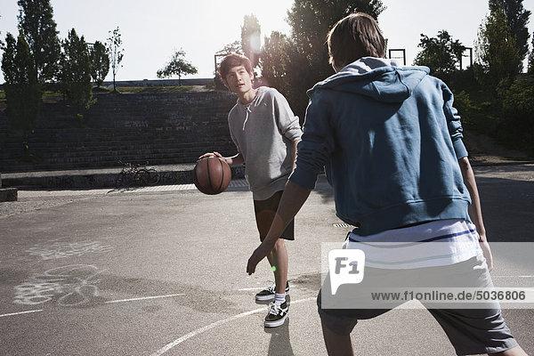 Jugendliche spielen Basketball auf dem Spielplatz. Jugendliche spielen Basketball auf dem Spielplatz.