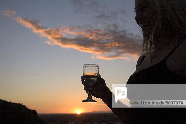 Frau genießen einen Drink gegen einen schönen Sonnenuntergang über den Strand  Jeffreys Bay  Südafrika