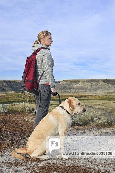 Frau Wandern mit ihrer männlichen yellow Labrador-Apportierhund in den Badlands  Drumheller  Alberta  Kanada