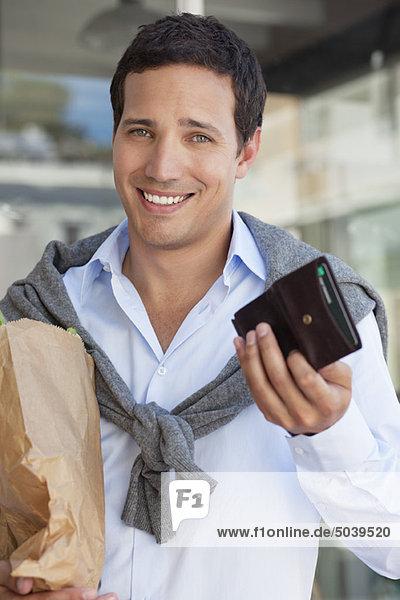 Porträt eines Mannes mit leerer Brieftasche und Papiertüte voller Gemüse