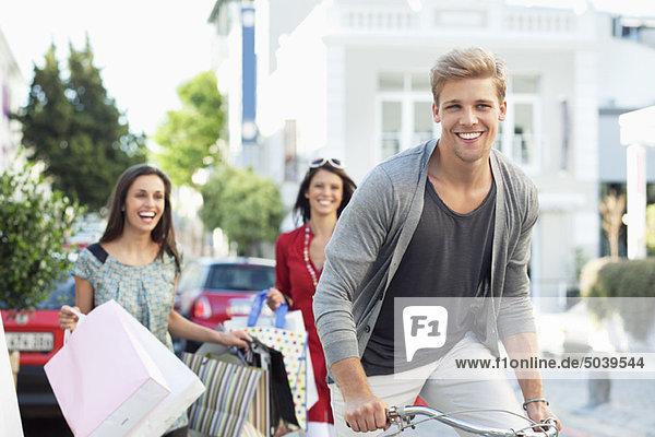 Junger Mann beim Radfahren mit zwei Frauen im Hintergrund