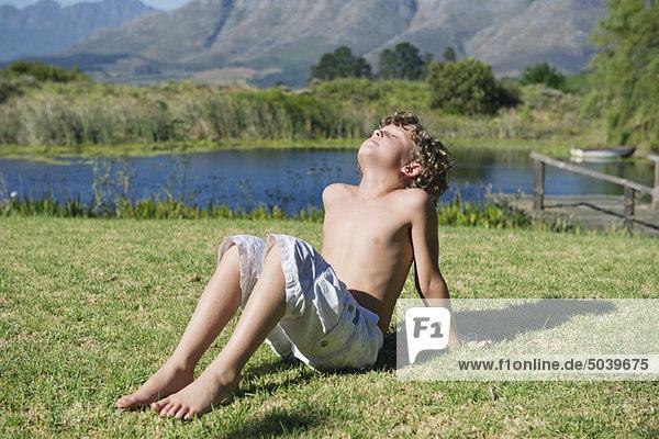 mit nacktem Oberkörper kleiner Junge sitzt mit seinen