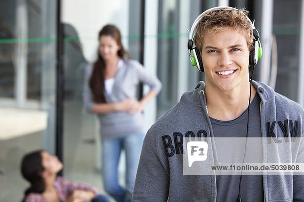 Portrait of a man listening to music with headphones in a campus