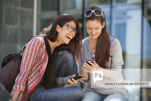 Two female friends using mobile phones
