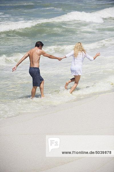 Rückansicht eines am Strand laufenden Paares