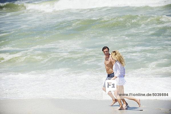 Seitenprofil eines am Strand laufenden Paares