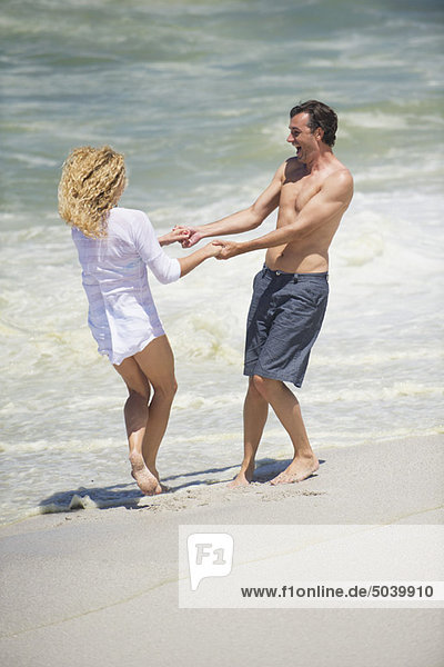 Mid adult couple playing on the beach
