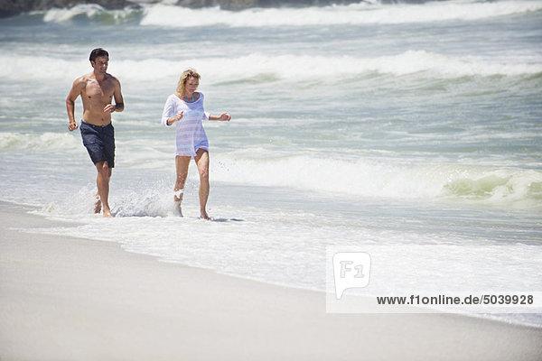 Mittleres erwachsenes Paar  das am Strand läuft