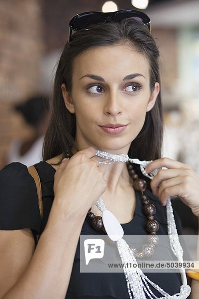 Junge Frau versucht eine Halskette in einem Einkaufszentrum Junge Frau versucht eine Halskette in einem Einkaufszentrum
