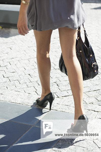 Ansicht einer jungen Frau  die auf einer Kopfsteinpflasterstraße läuft